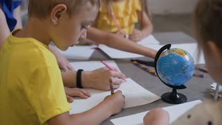 A group of children and a teacher draw on white paper using colored pencils. Primary school children drawing in the classroom with teacher helping, slow motion