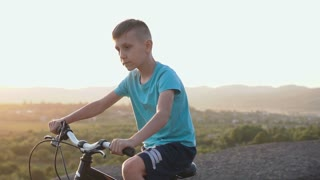 A handsome boy 8-9 old in a blue T-shirt rides a bike in a mountainous area against the background of the forest in the sunset or sunrise. A child riding a sporty black bicycle at the dawn at summer