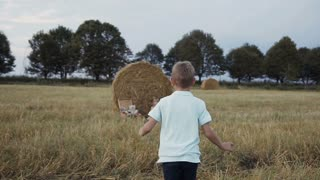 A little boy runs to a girl who sits in the field under the bale of straw. Happy girl in white dress smiling boy running to her. Sunset slow motion