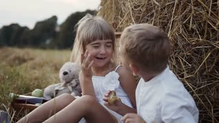 A little girl in a white dress wakes a boy who is eating a plum. Children in the field sit under the bales of hay slow motion