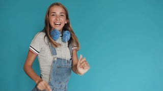 A little girl with big white teeth dancing on a blue background. Teen girl with bright, bright blue headphones, rejoices and jump near beautiful wall. Joy, smile and emotions. Slow motion.