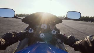 A motorcyclist riding a motorcycle on an empty asphalt road slow motion