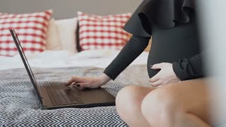 A pregnant girl wearing a black tight body with a collar works on an laptop at home and strokes her belly with her hands. A pregnant woman using on a laptop slow motion
