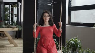A pregnant woman in a long red dress rides a swing and looks out the window. Smiling pregnant girl on a wooden swing. The concept of pregnancy - soon mother, motherhood, happiness, family slow motion