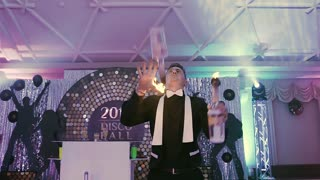 A professional bartender juggles with three bottles of fire at a disco party. The bartender is impressive, it's wonderful show on the holiday slow motion