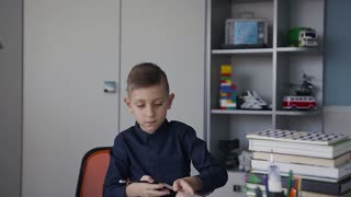 A pupil paints a picture of his homework at school. The boy has a ruler in his hands and a pencil. A student sits at home at home and does lessons slow motion