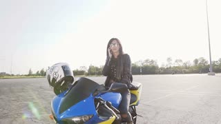 A young biker girl with dark hair in a leather jacket and sunglasses sits on her motorcycle and has fun talking on the phone slow motion