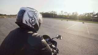 A young biker in a helmet rides on his motorcycle. Close-up slow motion