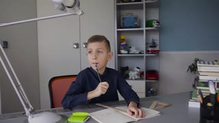 A young boy came up with an interesting idea how to do the homework that the teacher asked. Homework at home, notes in the notebook, pencil sketches in the notebook slow motion