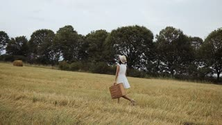 A young girl wearing a white dress with a straw hat and a suitcase. Straw and straw bales. Sunset slow motion