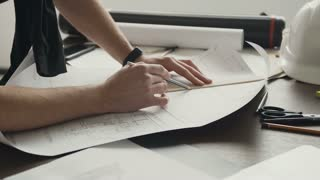 A young male architect is working on the project of new apartments. Husband is an architect draws a plan, graphic, design, geometric figures with a pencil on a large sheet of paper on the office desk