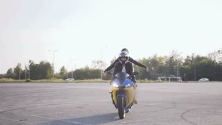 A young man and a young woman dressed in stylish clothes have fun riding a motorcycle. Young couple bikers on their motorcycle slow motion