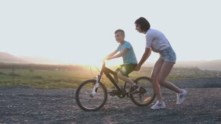 A young mother teaches her son to drive on a bicycle at summer in sunset or sunrise. A woman holds a bike on which her son learns to ride Happy family vacation, riding on bicycle, slow motion