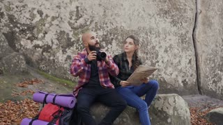 A young travel photographer with a camera, turist map and a backpack sitting with a young girl on a rock and looking at the sunset slow motion