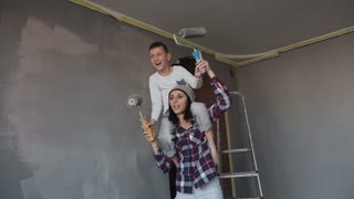 A young woman, along with her son, is washing the walls in the room and dancing fun. Repair in the new apartment. Funny work at home slow motion