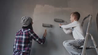 A young woman and her son have fun and whitewash the walls in a gray color at home. The boy is sitting on the ladder and paints a wall with a roller 4k