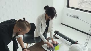 A young woman is an architect and designer working on the project of new apartments. Draft drawings and work on a laptop. Two colleagues of architects work in the office 4k