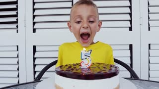 Adorable five year old boy sits for the table and celebrating his birthday blowing candles on white background. Close-up a cute boy blows out the candle on the cake. Birthday kid, 5 years old, slow