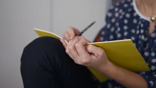 An attractive young woman in glasses sits at work table in the morning and makes some notes with a pencil in a notebook slow motion