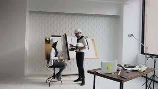 Architect and engineer discuss important work questions on the construction of a residential building on a construction site near a drawing instrument with a project slow motion