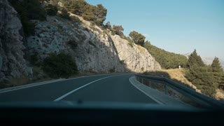 Asphalted mountain road with sharp sharp turn near the cliff. View from windscreen. Driving a car on mountain road. Nature Croatia slow motion
