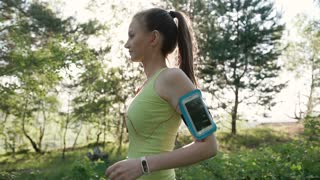 Athletic Caucasian young woman running and listening to music at headphone on smartphone at the outdoor in the forest at sunset. Athletic girl makes a jog in the park while listening to music, slow