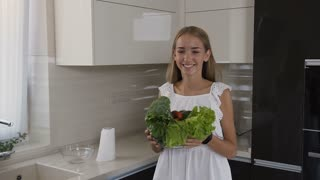 Attractive blonde girl in white dress carries glass plate with vegetables in hands in the kitchen. Mum and two daughters learning to chop vegetables together in the kitchen, using a chopping board and