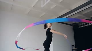 Attractive female gymnast dancing with colored ribbon in gymnastics school. Slimgymnastics in black body performs the gymnastics exercise with a ribbon in the white studio and possing to the camera