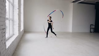Attractive female gymnast dancing with ribbon in gymnastics school at white background and look at the camera. Rhythmic gymnast, slow motion