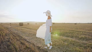 Attractive girl in a long dress, big hat with a scarf spins around herself in the field at sunset summer. Beauty young woman walking on yellow straw bales field. Freedom concept. Happy woman outdoors