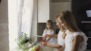 Attractive happy mother and her younger daughter wash the vegetables together in the kitchen sink getting to cook mixing salad, the older sister slicing an apple. Mom gives her daughter tomatoes for