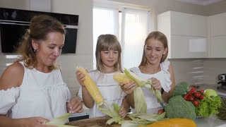 Attractive mom and her daughters cleaning the ripe ears of maize from leaves at home kitchen. Happy family is cleaning corn from leaves for cooking. Healthy food, slow motion