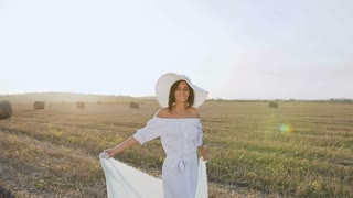 Attractive smili girl in a long dress, big hat with a scarf spins around herself in the field at sunset summer. Beauty, young woman walking on yellow straw bales field. Freedom concept. Happy woman
