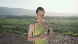 Attractive sport girl drinking cold water after running in the mountain in the fresh air during sunny day. Beautiful fitness athlete woman drinking water after work out, health and sport, sunset, slow