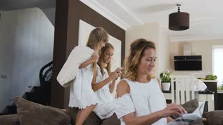 Attractive woman sits on the sofa and read the book while her lovely nice daughter jumping with soft pillow on the couch next to her at home. Wonderful happy family. Happy moments, slow motion