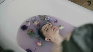 Attractive young woman in bath with milk and fragrant flowers of buds . Spa treatments for skin rejuvenation. Pretty sexy young woman relaxing in white bath with warm milk and colored flower buds