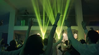 Audience with hands raised at a music party and lights streaming down from above the stage. Soft focus. A view from the dancing hall with raised hands slow motion
