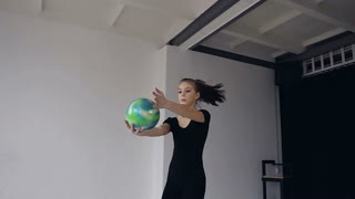 Beautiful blonde girl dressed in black sports body suit performs dancing with ball in gymnastics school. Gymnast with the ball in his hands doing acrobatic moves at sport indoor in the white