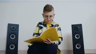 Beautiful boy in glasses with textbook sits on floor at home and records something in there interesting. The student does the job that was asked in school doing at home slow motion
