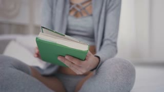 Beautiful brunette girl in glasses sits on the bed and holds a book for reading. A young woman opens an interesting book in a green cover at home slow motion