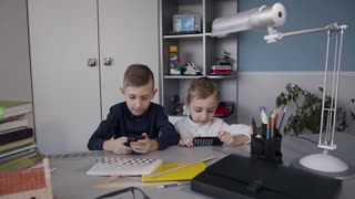 Beautiful children addicted to mobile phones playing games with concentrated faces. Two boys using the phone playing online games at home sitting at the table slow motion