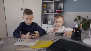 Beautiful children addicted to mobile phones playing games with fun faces. Two boys using the phone playing online games at home sitting at the table slow motion