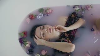 Beautiful fashion model girl in milk bath with fragrant flowers of buds, touching face skin. Spa and skin care concept. Beauty young woman with colored flowers is relaxing in milk bath, rejuvenation