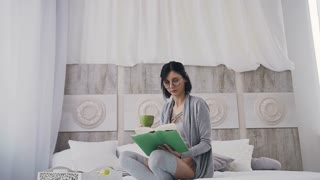 Beautiful girl in glasses sitting on a bed in a white bedroom, drinking a hot coffee from a green cup and reading a book in a green cover slow motion