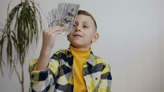 Beautiful little boy rejoices money. View of a boy Counting American 100 bills, boy happy about having money. White in background, indoor, slow motion