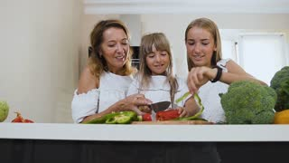 Beautiful mother teaches her younger daughter to cut a pepper with a knife and the older sister eats these vegetable at home in the kitchen. Little girl cooking together with loving mom and sister at