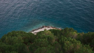 Beautiful view from the cliff mountain to the beach of Makarska through the pine forest. Dalmatia, Croatia slow motion