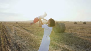 Beautiful woman in a light dress raises high up her charming baby boy and starts to spin around and smiles . Happy young woman spending time playing with son in the field at sunset, slow motion