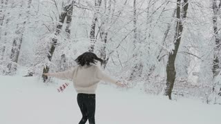 Beautiful young girl with dark hair in a knitted sweater with a scarf and knitted mittens walks in the winter forest during snowfall slow motion