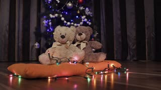 Blurred background of decorative Christmas tree, garlands and two toy teddy bears 4k